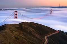 The sun sets as the majestic fog of the Pacific coast glides under the iconic Golden Gate Bridge. The long exposure of the fog reveals a silky texture as the low clouds rise and fall over San Francisco's trademark hills. All the while, tourists and locals alike make their drive along the mountainside, to try and capture the moment for themselves. Location: San Francisco, CA