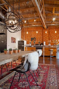 Quirky industrial boho kitchen and dining space in Mulu's Creative + Vintage Collective Den. Love the fur, Persian rug, pot plants, bare bulbs, exposed brick... Everything!