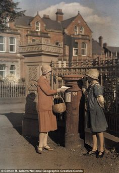 """March 1927, Ireland: Two girls send a letter at the red """"pillar box"""" of the Royal Mail"""