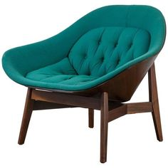 This unique vintage Mid-Century lounge chair was designed by George Mulhauser for Plycraft in the 1960's. It features a walnut frame that wraps around the chair and the original tufted teal upholstery.