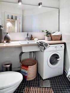 white bathroom black floor tile washing machine under countertop