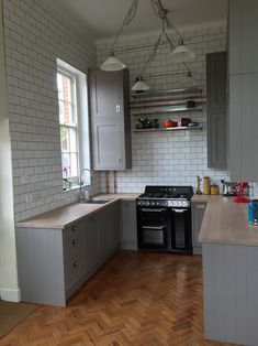My completed kitchen. B&Q carisbrook taupe (grey/gray) framed units, worktop express full stave oak worktop finished in chalk wax, franke centinox sink, exposed copper pipe work, inset handles, double height cabinets, tons of tiles metro flat tiles.