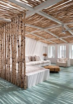 Love the thatched effect yet modern interior ceiling and shadows it makes. Like the trees as partitioning wall even more! Great way to bring the outdoors in, create zones and spaces in rooms and still let light in. Wonderful.