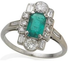 An art deco emerald and diamond ring, 1920s.   Of geometric design, the central plaque set with a step-cut emerald surrounded by baguette, single and old brilliant-cut diamonds, between baguette-cut diamond shoulders, emerald approximately 0.67 carat, diamonds approximately 0.60 carat, ring size J½. Bonhams.