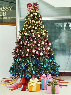 Give your tree a rainbow effect by organizing bulbs in monochromatic sections along the tree. Here, shades of yellow, pink, and blue create the desired effect. Connect the colors by adding a tree topper and skirt that uses all the colors on the tree. Learn how to make the colorful ribbon tree skirt on the next slide./