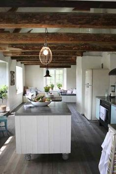 Spotted (and admired) on Emmas Designblogg, an appealing rustic kitchen by Isabelle Halling, a Swedish interior designer. Halling mixes a lighting fixture fashioned from an industrial whisk with glossy white tiles, sleek black appliances, a kitchen island on wheels, and pale blue cabinets.