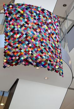 I am in love with this. Oh, my gosh, I would almost be crazy enough to try it. This woman used scrap sock yarn and US1 needles to knit all these squares to make a gorgeous blanket.