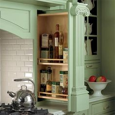 Hiding behind this painted pilaster is a two-tier pull-out shelf that keeps condiments within arm's reach of the range.   Photo: courtesy of Plain & Fancy Custom Cabinetry   thisoldhouse.com