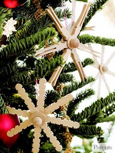 Give your tree a natural feel by making these simple snowflakes. Glue together Popsicle sticks or clothespins in an asterisk, then add a wood craft round and ball to the center. Hang using baker's twine.