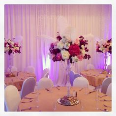 Great Gatsby inspired Quinceanera. Unusual color combination that works!  Flowers on top of a crystal pedestal from @Baker Party with crystal@garland giving it a very elegant look. Of course ostrich feathers!! #paulfennerfloraldesign #flowerstagram #flowers #centerpieces #tablecenterpieces