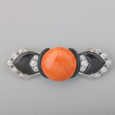 ART DECO CORAL, DIAMOND AND ENAMEL PLATINUM BROOCH. Button-shaped orange coral, 19.4 mm. centers modified bow-shaped brooch set with OMC diamonds, approx. .82 ct. TW, #90087. Ca 1935.