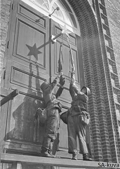 Finnish soldiers tearing off red star from the door of the church soon after Finnish troops liberated area. Jaakkima 1941.08.08