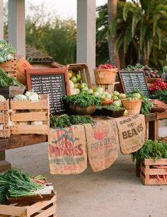 Rustic farmer's market display with burlap sacks & chalkboard menu.