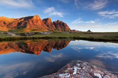 Red dawn light lights up the peaks known as The Three Bushmen as high clouds streak the sky.