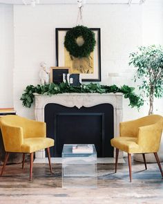 A pair of golden-yellow armchairs and a transparent coffee table surrounding a mantel decorated with greenery