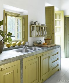 The kitchen countertops are poured concrete, and the doors, window frames, and custom cabinetry are all painted in a custom color.