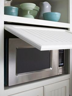 "Move the Microwave Behind Closed Doors:  ""Give your kitchen a cleaner look by concealing the microwave. This microwave fits into a cubby, and a slide-back door makes it easily accessible without taking up a single inch of counter space."""