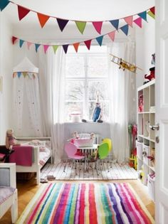 White with added colour. Table and chairs under the window, bunting, fabric cot 'tent' colourful rug.