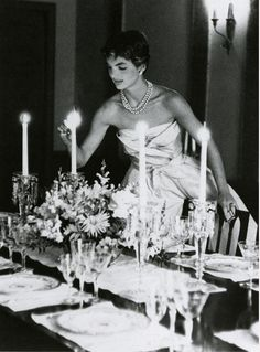 Jackie O lighting candles for a small dinner party in her home.