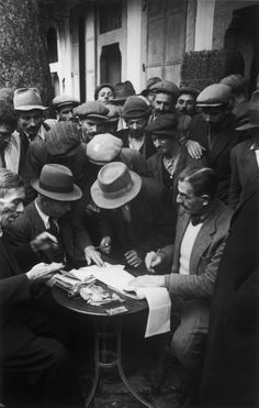 Robert Capa - Turkey.1946. A tobacco broker surrounded by farmers trying to sell their crops.