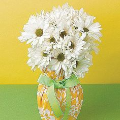 Transform your ordinary glass vase into a colorful centerpiece. All you need is a pretty cloth napkin and some bright ribbon.
