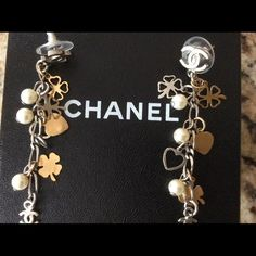 Authentic Chanel dangle earrings with charms These are authentic Chanel pierced dangle earring with faux pearls, silver & gold tone charms. They are 2 1/4 inches long. Very little tarnishing. Great condition. Comes with box. This is on other sites, may go fast. CHANEL Jewelry Earrings