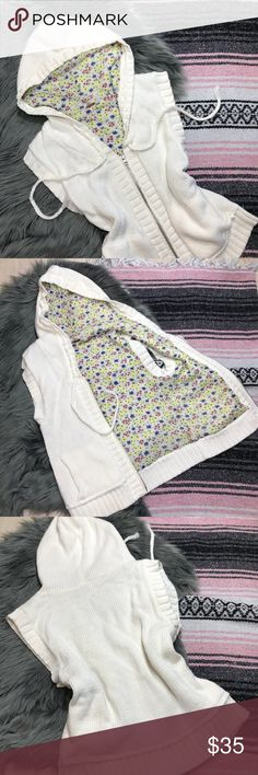 Free People zip hoodie sleeveless cream & floral M Cool in the morning, but warm in the afternoon? This hoodie has your waffling weather covered! Floral print inside this beautiful cream colored sleeveless medium hoodie. Braided ties weave around the hood to cinch it closed. Double silver zipper for zipping up or down, front pockets, ribbed bottom and sleeve hems. Super-soft hooded sweater vest from Free People!  Tags: free People, sweater, hoodie, sweater vest, sleeveless, knit  Specs…