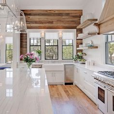 Rustic reclaimed wood with black trim windows are a nice contrast in this white kitchen