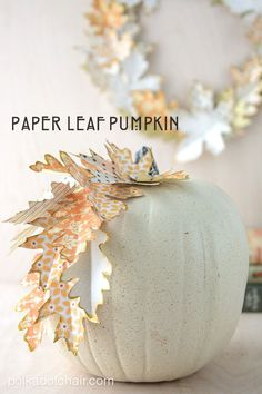 Use cut paper leaves decorate a pumpkin for fall.