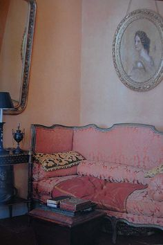 Mid pink sofa against light pink walls in a shabby chic French chateau style living room.