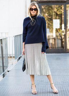 A saia plissada voltou! No comprimento midi, é apropriada pro trabalho e até pra algum evento mais fino. Nesse look, a saia prata ficou super descolada combinada com o suéter azul.