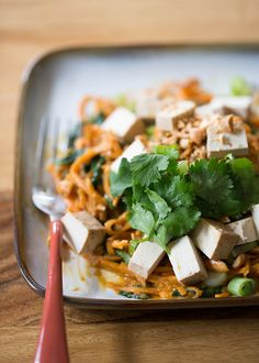 Spiralized sweet potatoes tossed with spinach, drenched in peanut sauce, and topped with crunchy peanuts. Increase the protein factor by topping with baked tofu or - if any carnivores are at your table - some grilled chicken. #vegan #onedishtwoways #sweetpotatonoodles