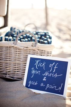 Cute sign with a basket of flip flops for the reception.