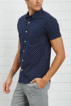 A fitted woven shirt with an allover abstract print, basic collar, buttoned front, chest patch pocket, and short sleeves.
