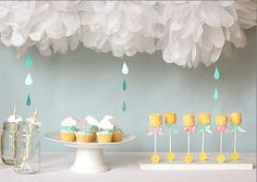 Gender neutral April showers baby shower theme decorations with homemade tissue paper cloud and rain drops mobile printable umbrella cutouts for games and advice and rattle cake pops in blue and yellow in a decorated stand