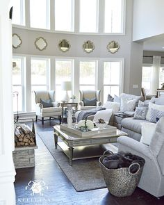 Kelley Nan (@kelleynan) • Instagram Neutral white and greay Two 2 story lving room great room with quatrefoil mirrors between bow of windows- large gray sectional sofa and blanket basket and zgallerie palais collection coffee table KELLEYNAN.com