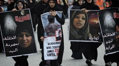Bahraini women hold portraits of female prisoners during a rally in Janosan Village, in the western suburb of Manama, on May 18, 2012.