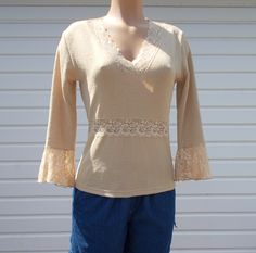 New Item Susan Lawrence Beige Blouse size medium Material is polyester Made in the USA 3/4 sleeve pretty lace detail around v neck and sleeve I only ship to the USA - $15.99