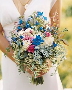 Blue delphiniums highlight this bouquet of coral bells, artemisia, Queen Anne's lace, and pink and white roses.