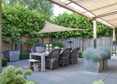 Bij deze onderhoudsvriendelijke tuin zijn robuuste materialen gebruikt. Het terras van bamboehout zorgt voor een fraaie onderbreking van de betontegels. Als afwerking zijn tussen de bamboeplanken rubber strips aangebracht. De leiplatanen geven de tuin intimiteit. Als zonwering is schaduwdoek aangebracht. Behalve leiplatanen die voor de nodige privacy zorgen bestaat de beplanting hoofdzakelijk uit buxus, hortensia's, een notenboom en twee oude perenbomen (Conference) in grote houten kuipen.