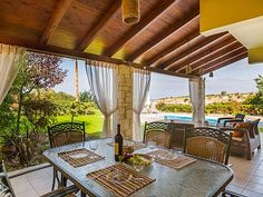 Rethymno villa rental - Outdoor dining and siting areas at the shaded veranda by the pool!
