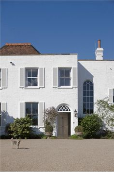 A house with exterior in Wimborne White Exterior Masonry, shutters in Wimborne White Exterior Eggshell and door in Fawn Exterior Eggshell.
