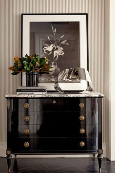 Black lacquer chest with modern sculpture accessory, and fresh magnolia cuttings.