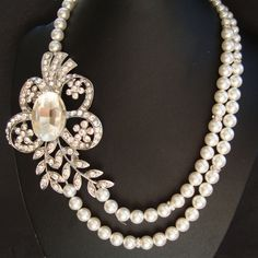 The Eve statement bridal necklace features a glamorous rhodium plated rhinestone flower and leaves pendant, offset from double strands of Swarovski pearls on one side and a single strand of pearls on the other. The pendant measures 3.5 x 2.5. Length is based on the inside strand length.  { Pearl Color } The 1st choice/shade pictured is Swarovski white- a soft bridal white with subtle shimmer, works with a huge range of shades from white to ivory, very versatile shade by far the most comm...