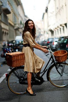 I love my fixed gear, but seeing photos like this make me want to go get my Mixte and put woven baskets on it and ride around in a pretty dress.  via The Sartorialist.