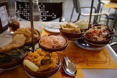 Gastronomia de Sevilla se basa en la dieta mediterranea platos tipicos: tapas, pinchos morunos(unas brochetas de carne a la barbacoa) las huavas de sabalo con mahonesa, pavias de pescado. Ensaladas, cauelas con guisos, embutidos, gambas, gapacho andaluz, serranitos, patas alinnas, si hay corrida de toros cola de toro. Ah, aceitunas. Polvorones,torrijas, alfajores, yemas de San Leandro, magdalenas.
