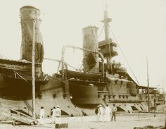 Battleship Tsesarevich Interned at Qingdao, 1904 showing the battle following the Battle of the Yellow Sea (Aug. 10, 1904) illustrating the vulnerability of French-designed battleships of the pre-dreadnought era. Not only are the funnels peppered with shot and ripped apart by shellfire, impairing draft to the boilers, there are multiple shell-holes in the unarmored upper works of the hull and a direct hit on the bridge (which led to the default loss of the battle.