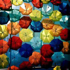 Hundreds of Colorful Umbrellas Floating Above Streets in Agueda, Portugal. Photo Patricia Almeida. #artinstallation #outdoorinstallation #umbrellas #colorful #agueda