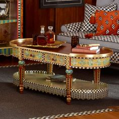 Revel in the rich jewel tones and textural collage of the Highland Collection. The Highland Coffee Table is detailed by hand with gold leaf, Courtly Check, faux marbling, polka-dot fringe, and lacquer-finished antique newspaper and Florentine papers. Imported wood frame, hand decorated in Aurora.