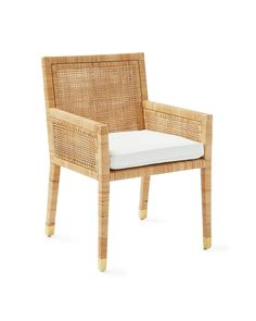 We've always admired rattan and its power to elevate without a lot of fuss. Here, artisans start with a beautifully proportioned mahogany frame and achieve gorgeous texture by weaving the rattan to display subtle variations in tone. Everything about this chair reflects thoughtful design – from the gently angled lines to the brass end caps on each leg. It's a great way to bring some natural glamour to the table. Comes with a perfectly tailored cushion.